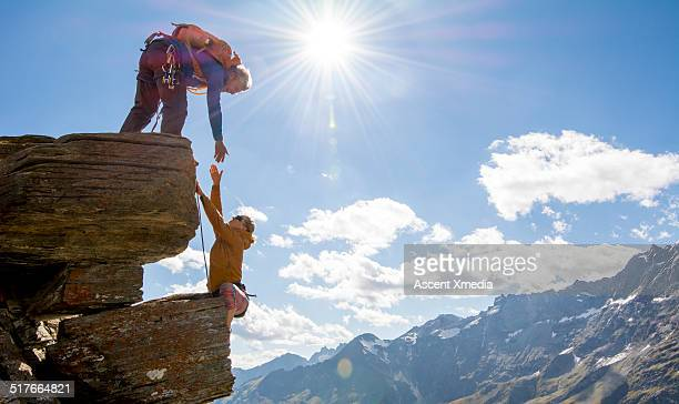 climber extends helping hand to teammate, mtns - valle d'aosta foto e immagini stock