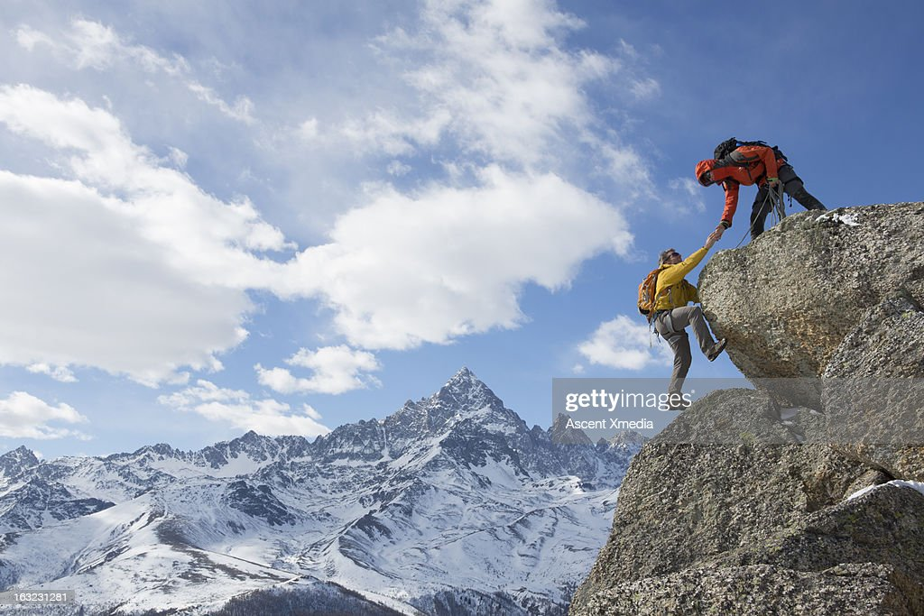 Climber extends helping hand to teammate : Stock Photo