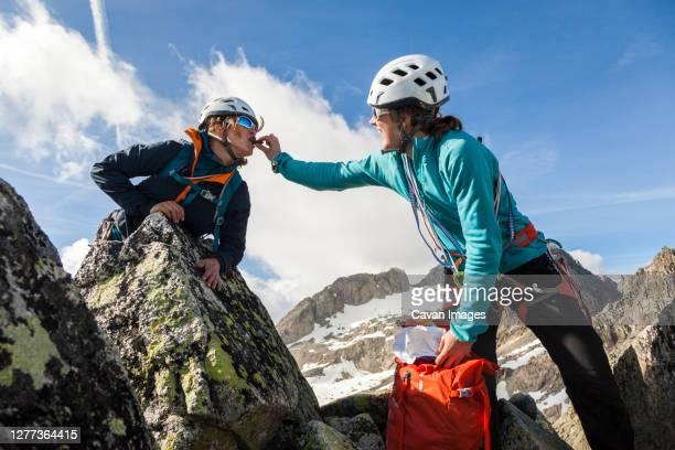 climber feeds partner chocolate, klein furkahorn, valais, switzerland - klein bildbanksfoton och bilder