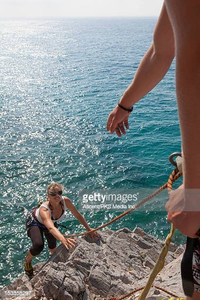 Climber gestures to teammate, on sea rock cliff