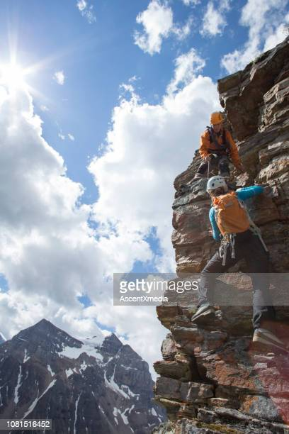 climber gives a helping hand to other climber - ascent xmedia stock pictures, royalty-free photos & images