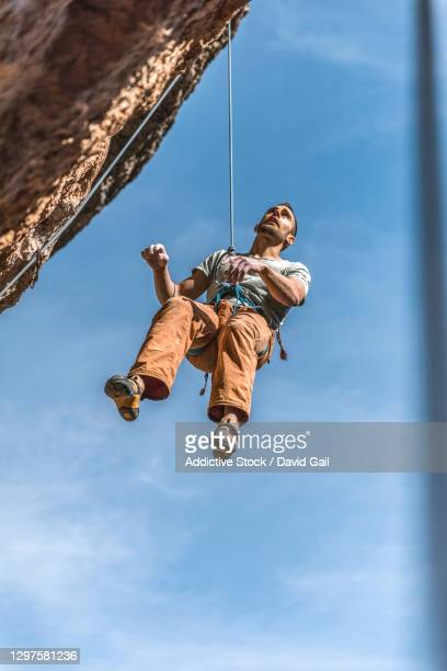 climber hanging on cliff - david cliff stock pictures, royalty-free photos & images