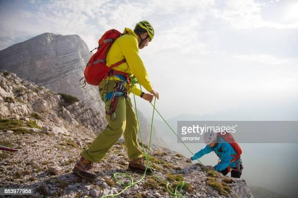 Grimpeur aidant la falaise abrupte de son coéquipier montée
