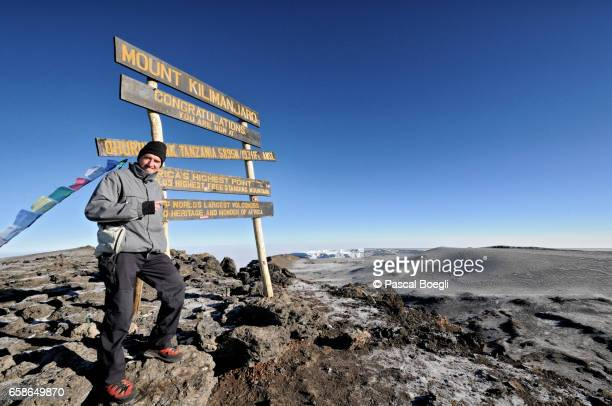 climber in front of uhuru peak sign, the top of mount kilimanjaro - kilimanjaro stock photos and pictures