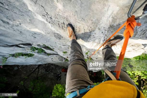 montanhista na parada da segurança na parede da rocha, pov - ângulo esporte - fotografias e filmes do acervo