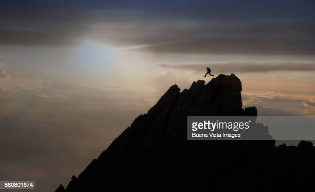 Climber jumping on a rocky ridge