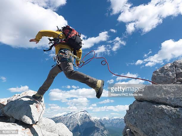 climber jumps across rock gap, makes contact - treten stock-fotos und bilder