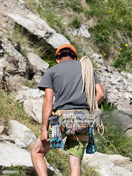 Climber loaded with the whole material opposite to a rock wall in the pirineos, France