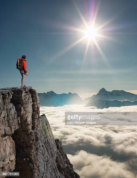 Climber looking out from peak emerging from fog in the Alps, Bettmeralp, Valais, Switzerland