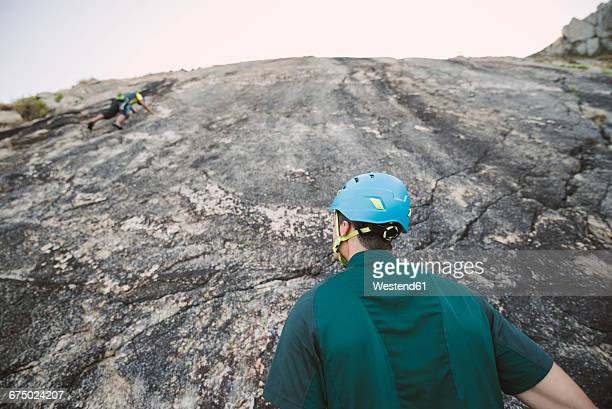 climber looking up a rock wall - rotswand stockfoto's en -beelden