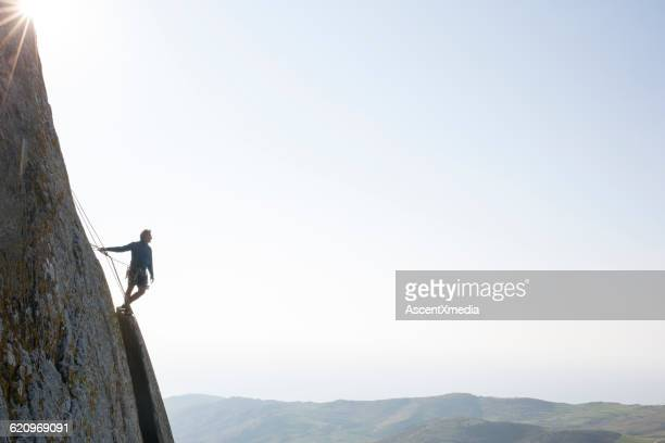 Climber looks off from edge of steep rock cliff