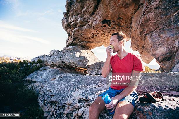 Climber Man eating apple during rest from extreme rock climbing