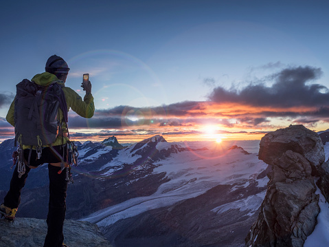 Climber on a peak photographing sunrise with smart - gettyimageskorea