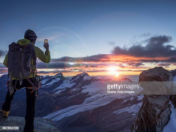climber on a peak photographing sunrise with smart - color climax stock pictures, royalty-free photos & images