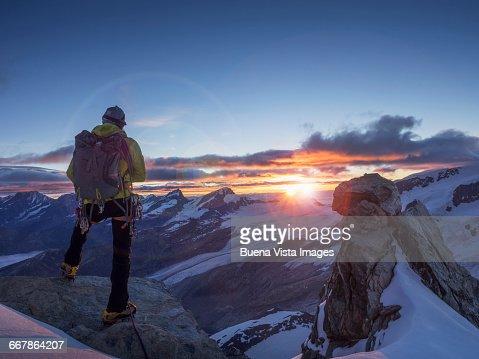 Climber on a peak watching sunrise
