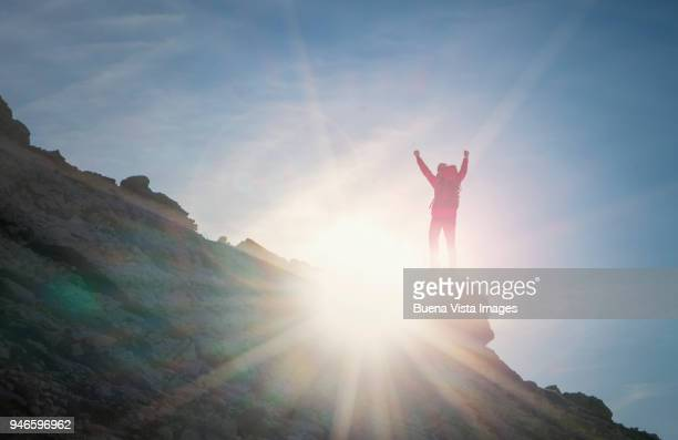 Climber on a rock exulting toward there sun