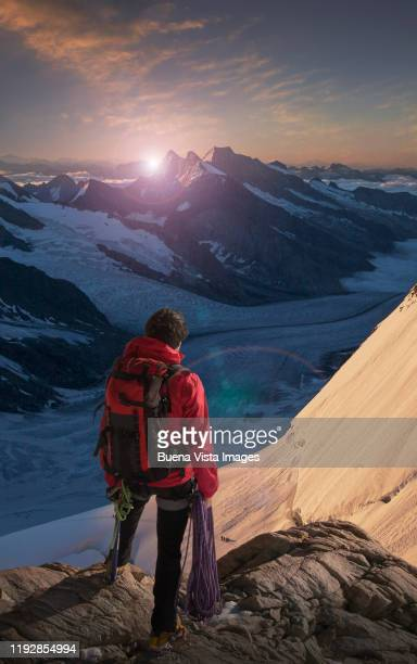 climber on a rock watching glacier - red coat stock pictures, royalty-free photos & images