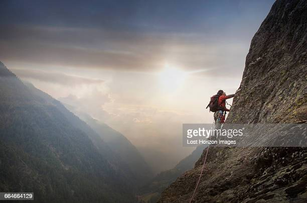 Climber on a rocky wall above a valley, Alps, Canton Bern, Switzerland