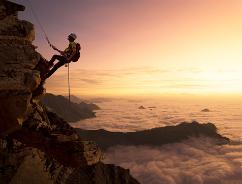 Climber on a rocky wall over clouds - gettyimageskorea