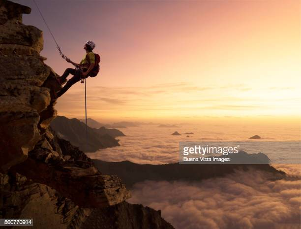 Climber on a rocky wall over clouds
