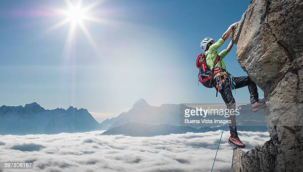 climber on a rocky wall - climbing stock pictures, royalty-free photos & images