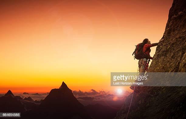 Climber on a rocky wall with the Matterhorn at sunset, Zermatt, Canton Wallis, Switzerland