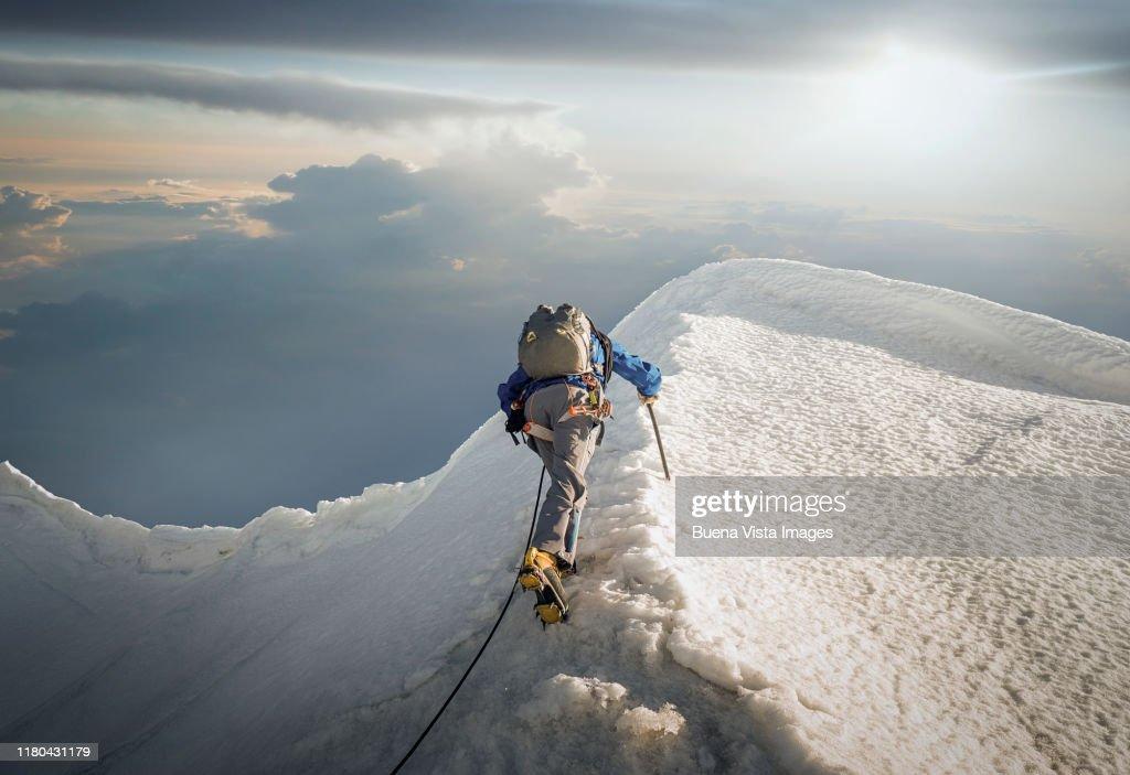 Climber on a snowy ridge : Stock Photo