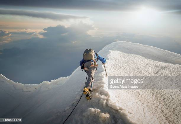 climber on a snowy ridge - vastberadenheid stockfoto's en -beelden