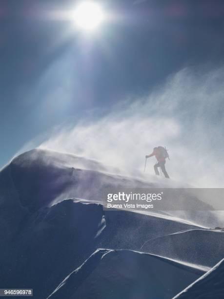 climber on a snowy slope in a snow storm - alleen één man stockfoto's en -beelden