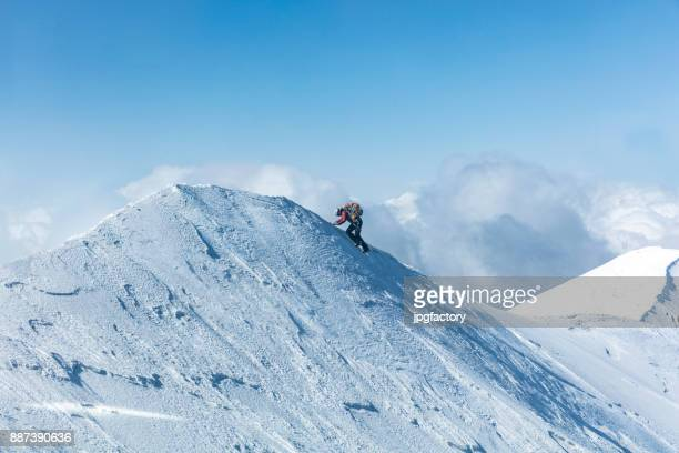 climber on the top of a mountain in winter