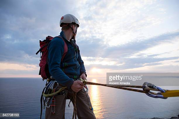 Climber pauses in descent, looks back to sea, sun