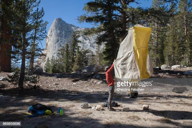 climber pitching tent in front of charlotte dome, eastern sierra nevada, california, usa - christina felschen stock pictures, royalty-free photos & images