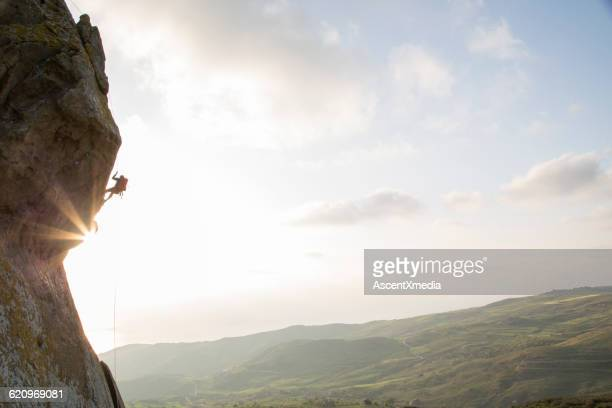 Climber prepares to descend from overhanging cliff