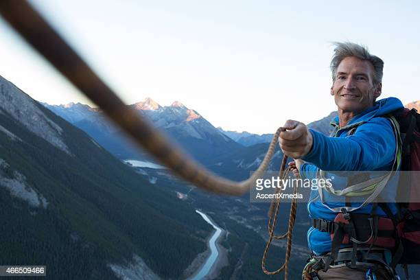 climber pulls rope tight for teammate - guidance stock pictures, royalty-free photos & images