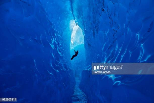 climber rappelling into cave - spelunking stock pictures, royalty-free photos & images