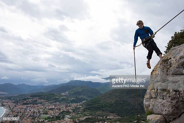 Climber rappels (abseils) at cliff edge above town