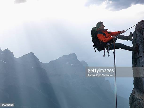 climber rappels (abseils) down cliff, mtns behind - rock climbing stock pictures, royalty-free photos & images