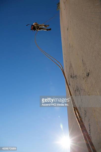Climber rappels down smooth marble slab, sunrise