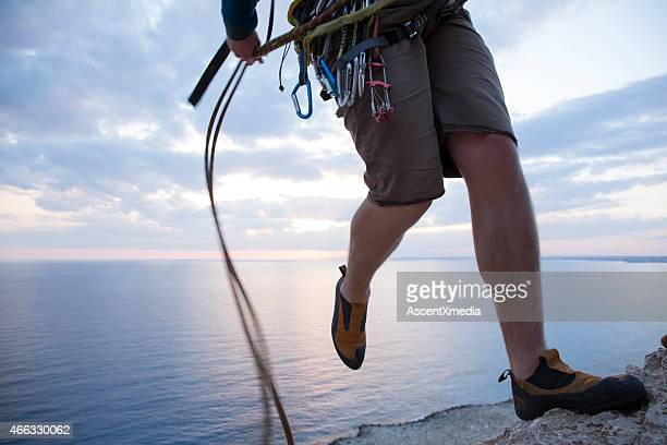 Climber rappels (abseils) from top of cliff