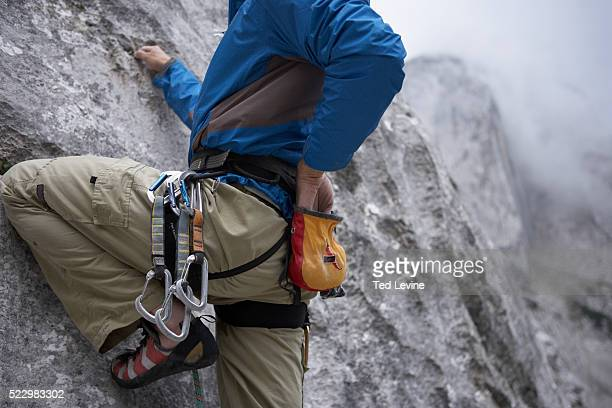 climber reaching into chalk bag - chalk bag stock pictures, royalty-free photos & images