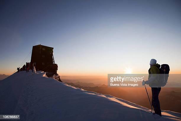 climber reaching mountain refuge. - monte rosa foto e immagini stock