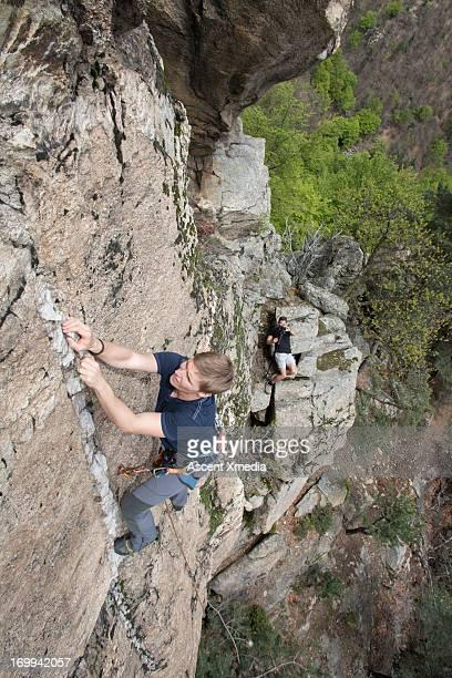 Climber scales vertical rock, man takes pic below