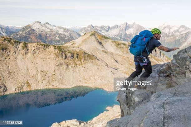 climber scrambles up a rocky ridge on douglas peak, b.c. - スクランブリング ストックフォトと画像