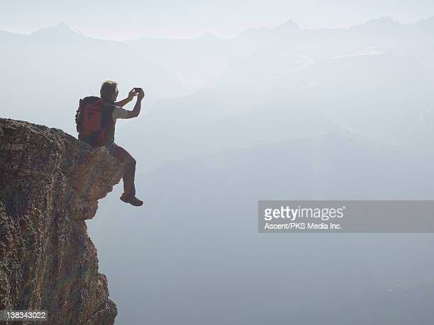 Climber sits on edge of overhang, takes picture