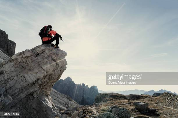 Climber sitting on a rock and watching a mountain range.
