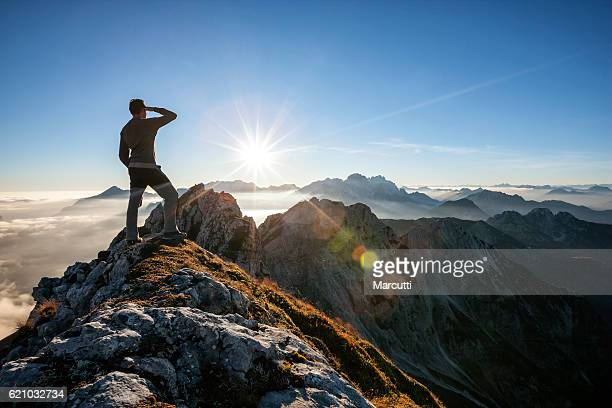 climber standing on a mountain peak - high up stock pictures, royalty-free photos & images