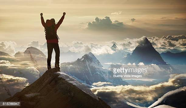 climber standing on a mountain summit - oben stock-fotos und bilder