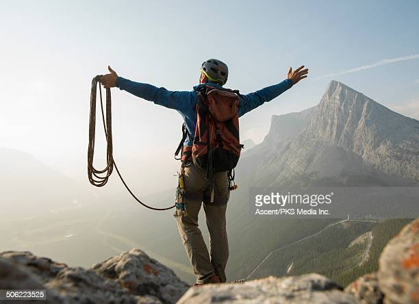 Climber stands on summit rocks, arms outstretched