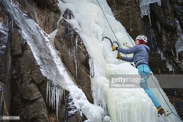 A climber swings her icetools on an icefall in the Pitztal valley on January 11 2017 near Graslehn Austria Winter weather arrived in Germany and...