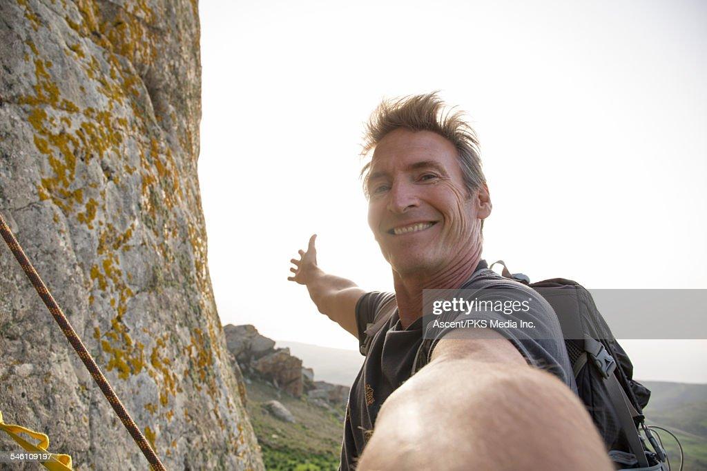 Climber takes selfie form mountain wall, above sea : Stock Photo
